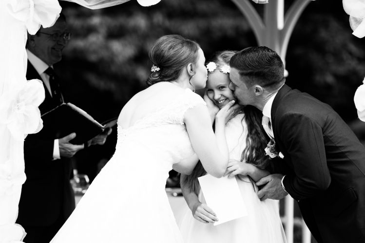 Bride and Groom kiss flower girl at the Rowhill Grange Hotel in Kent