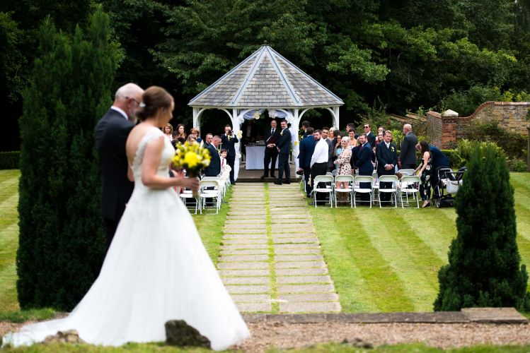 A happy groom waits eagerly as his bride to be walks down the aisle at Rowhill Grange Hotel