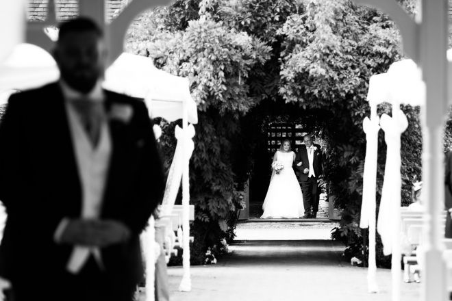 bride walks up the aisle at the Old Kent Barn Wedding Venue - Scott Kendall Photography
