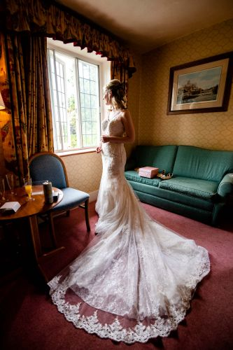The bride waits eagerly as the guests gather bellow ready for the wedding ceremony at Howfield Manor