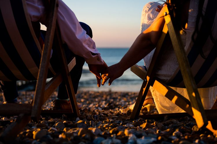 Bride and Groom hold each others hand as they watch the sun go down of The East Quay Venue on Whitstable Beach