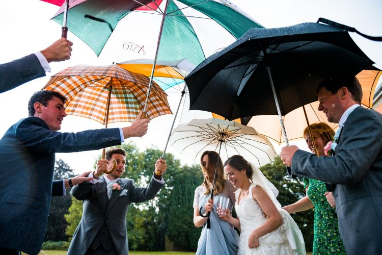 Ushers hold a lot of umbrellas over the bride as she walks through the rain at Mount Ephraim Gardens in Kent