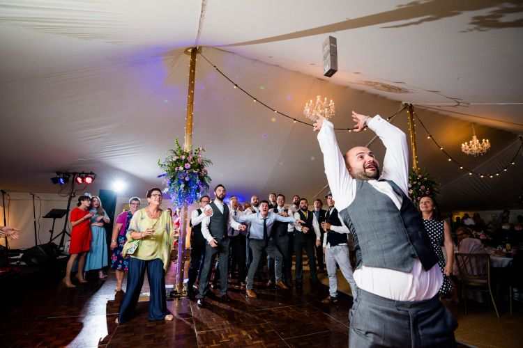 Groom throws a bottle of whiskey at a wedding reception.